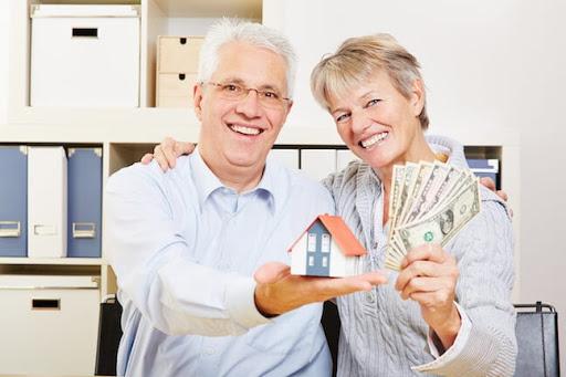elderly couple holding home replica, cash, blue button up shirt