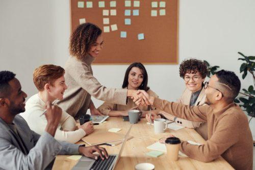 teamwork, meeting, handshake, coffee cups, brown sweater, wood desk, cork board, post-it notes, teamwork