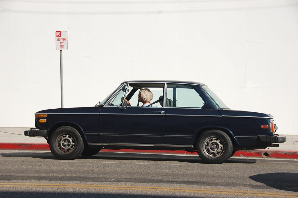 """An old woman drives a car in front of a """"No Stopping Any Time"""" sign"""
