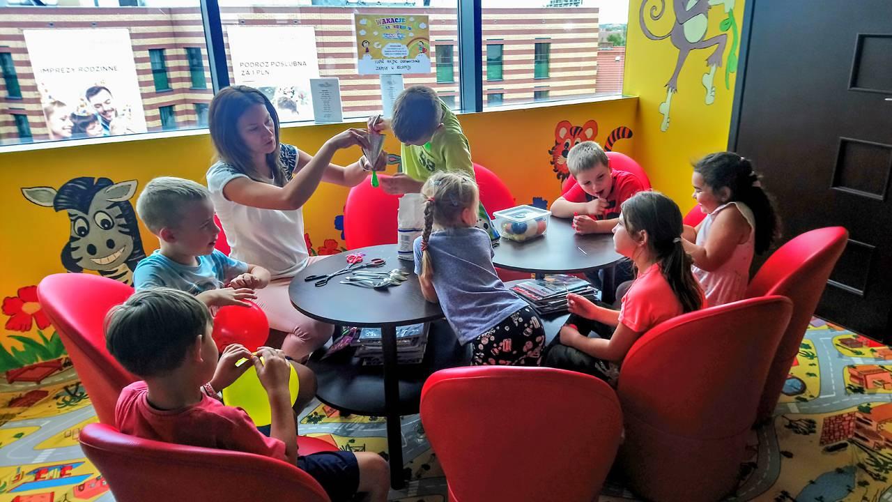 Zaj臋cia manualne w sali zabaw. Dzieci wok贸艂 sot艂贸w, wykonuj膮 tzw. gniotki.