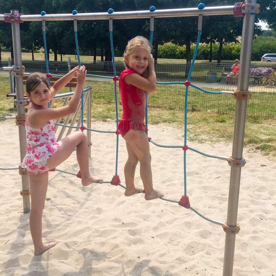 Plac zabaw w parku. Dziewczynki wpinaj膮 si臋 na siatce.
