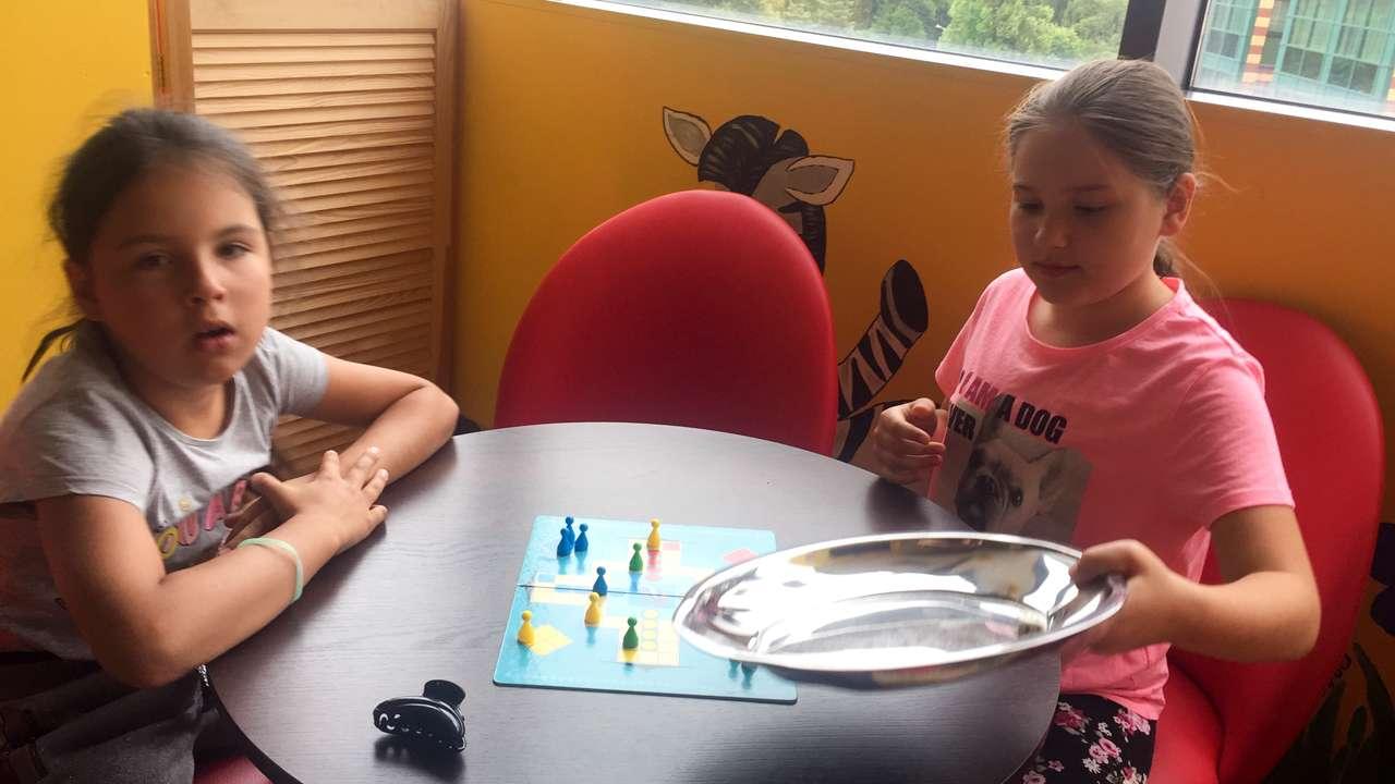 Dziewczynki przy stoliku graj膮 w chi艅czyka.