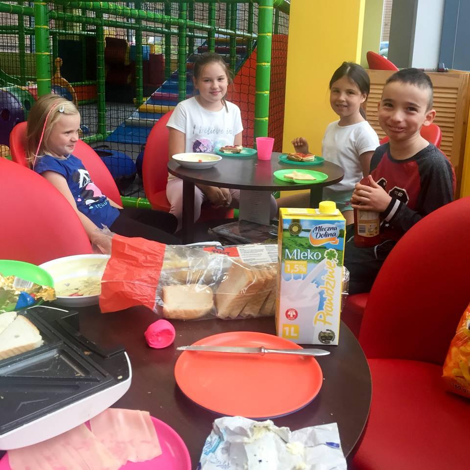 Dzieci u艣miechaj膮 si臋 nad talerzami. W trakcie pieczenia tost贸w.
