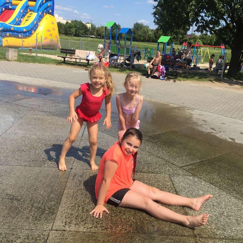 Mokre dziewczynki uchachane zabawÄ… przy fontannie w parku.