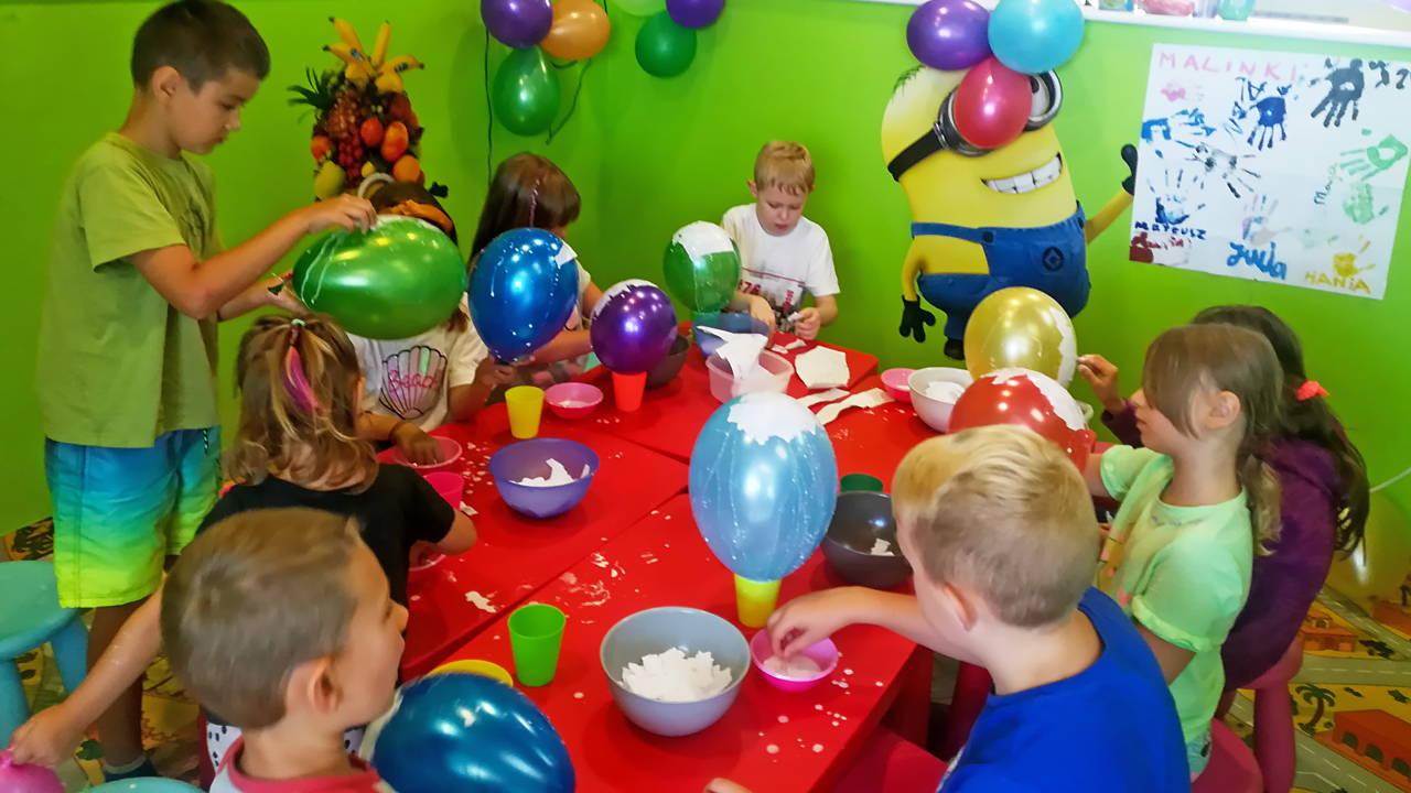 Dzieci tworzą piniaty na bazie nadmuchanych baloników. Warsztaty plastyczne.