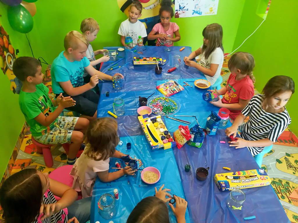 Dzieci przy wspólnym stole ozdabiają słoiki. Warsztaty plastyczne.