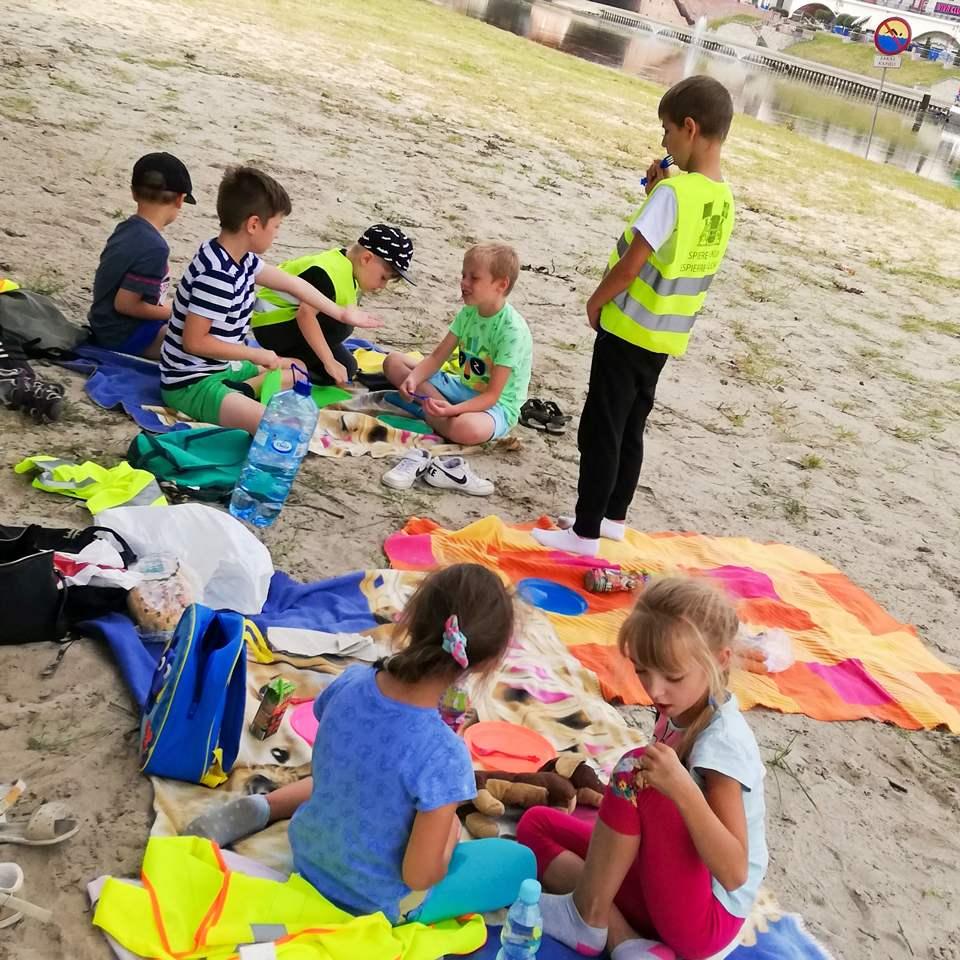 Dzieci siedzą na kocach rozłożonych na piasku plaży