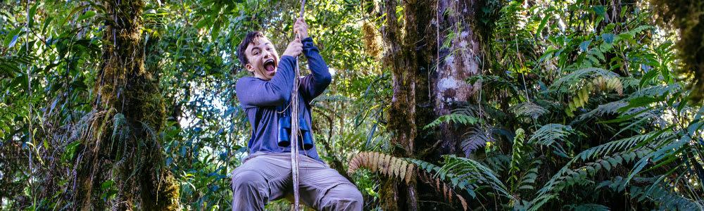 Teenage boy zip-lining in a jungle