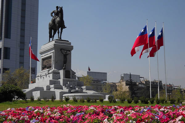 Statue in chile with flags beside
