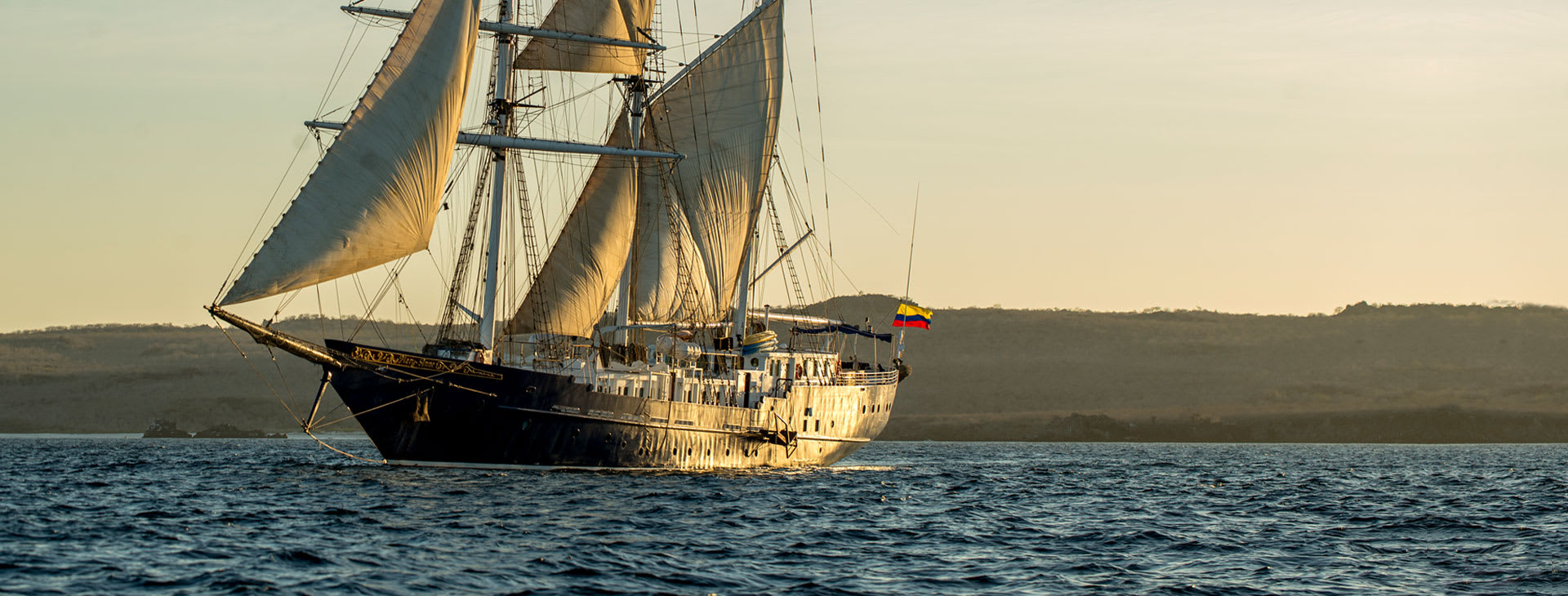 Ship with sail raised in the sunset light