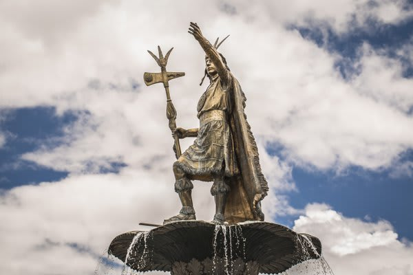 Statue of Inca in Cusco with clouds behind