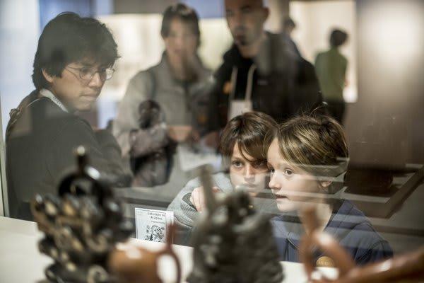 Kids peering through window at scupltures