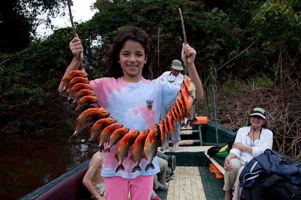 kid holding up piranha catch