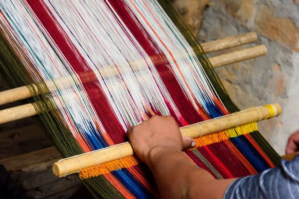Andean Weaver with Loom multi colored fabrics