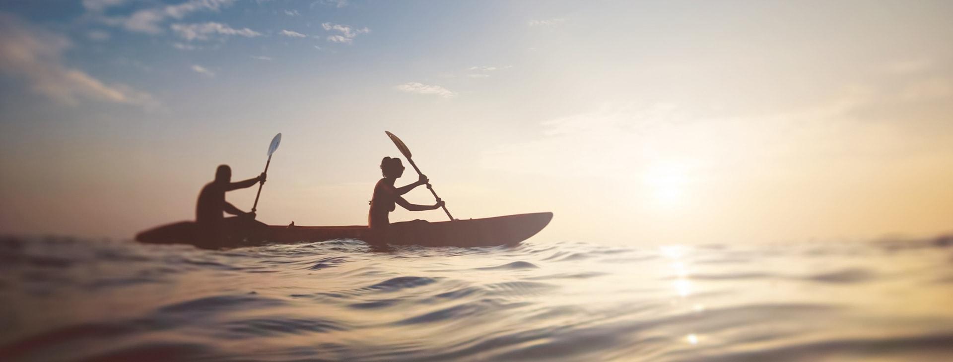 People on sea kayak at sunset