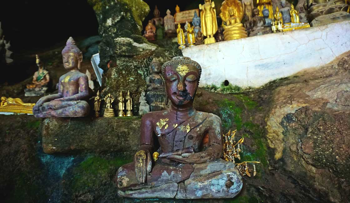 Old Buddha statuette inside the cave