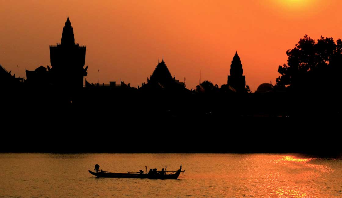Silhouettes of temples by the river
