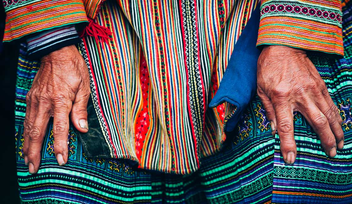 Hands of an elderly dressed in traditional clothes