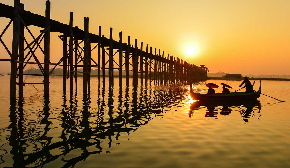 Boat approaching tall bridge at sunset