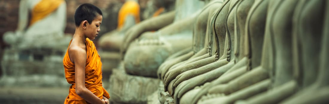 Young monk in front of Buddha statues