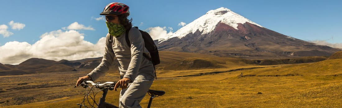 A person on a bicycle and mountain in the background