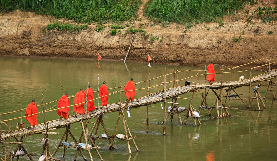 monks walking on a bridge