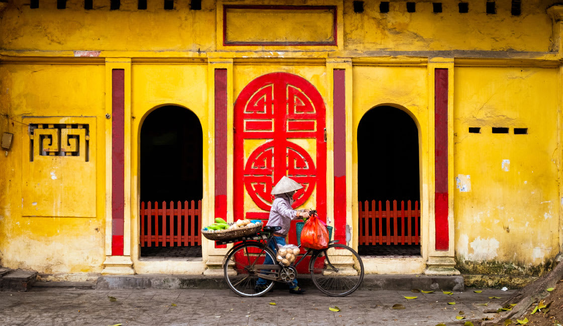 Vietnamese man in conical hat in from of the temple