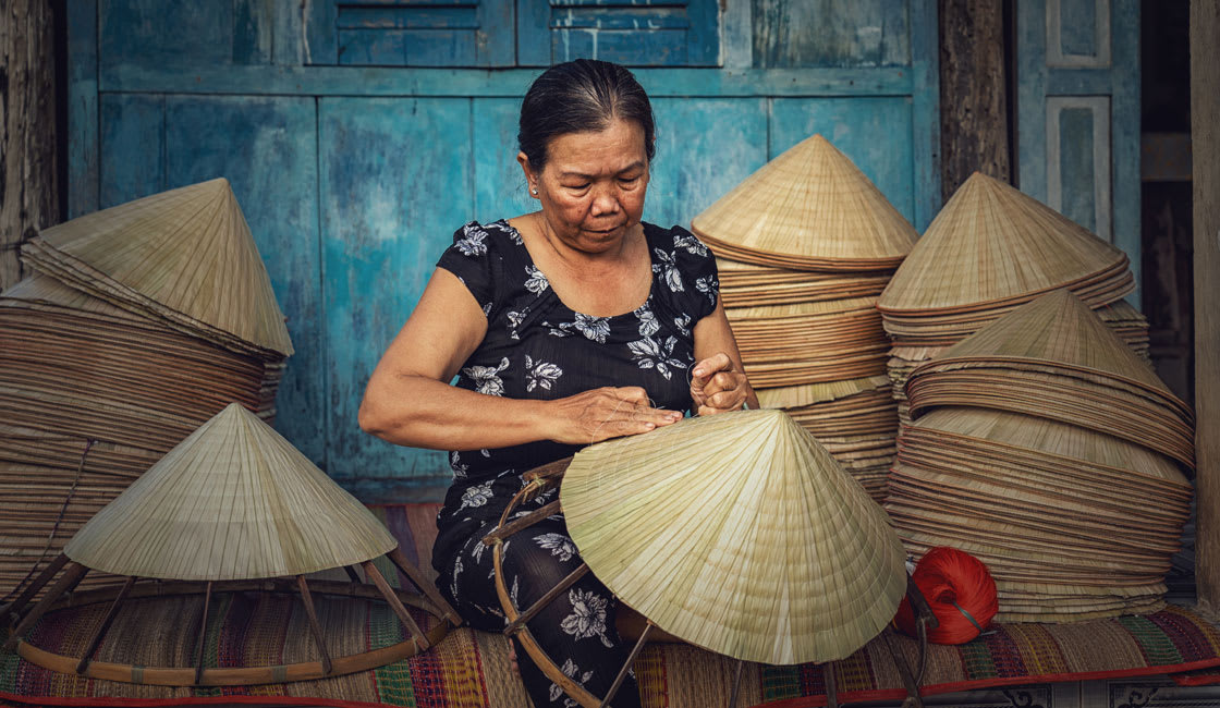 A Vietnamese woman making hats by hand on the porch
