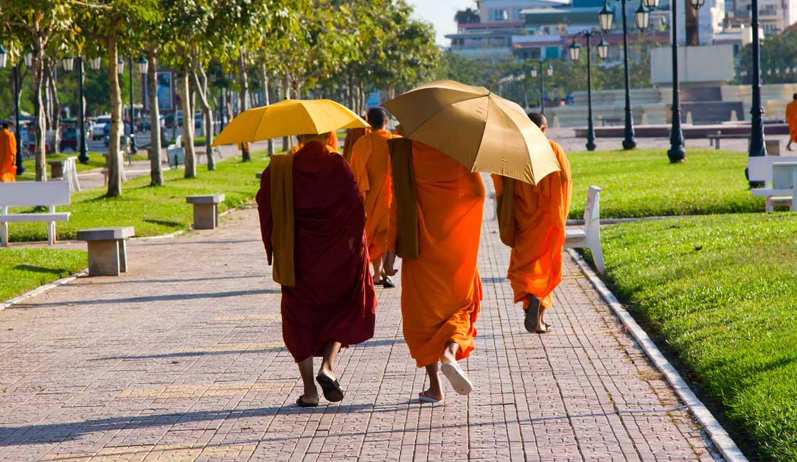 Monks walking under the orange umbrrellas