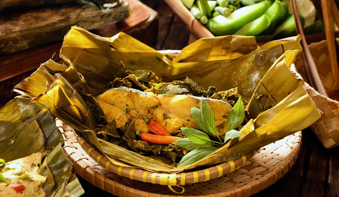 A fish baked in and served on a banana leaf