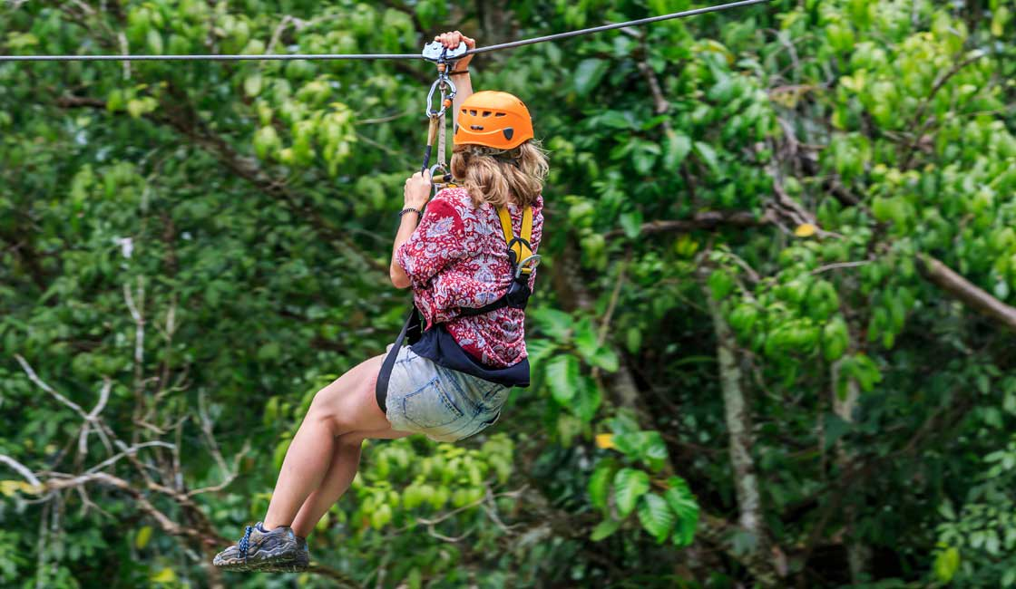 A girl zip-lining in the forest