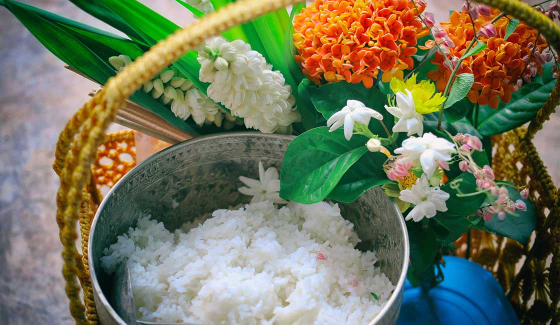 A basket with rice and flowers as an offering to a monk