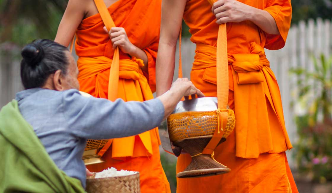 An elderly woman giving alms to monks