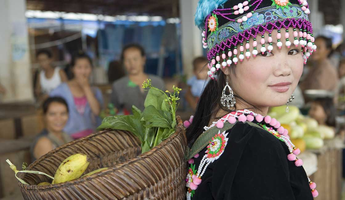 Hmon woman with decorated headpiece and basket on her back