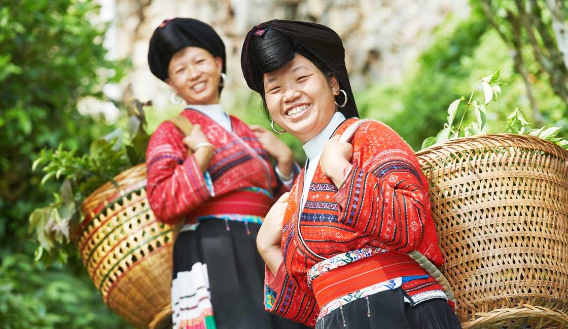 Two Yao women carrying baskets