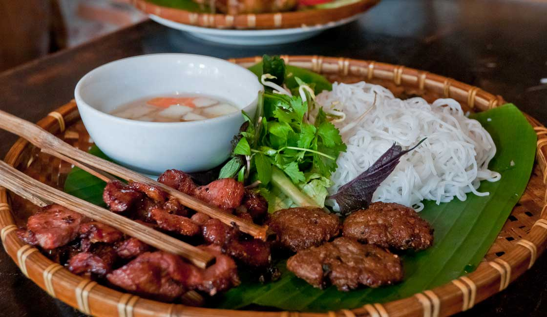 Grilled meat with rice noodles on a banana leaf