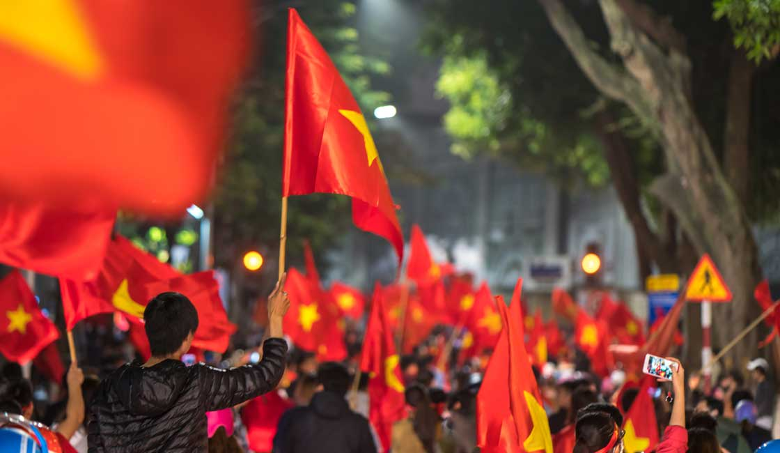 Street filled with people carrying Vietnamese flags