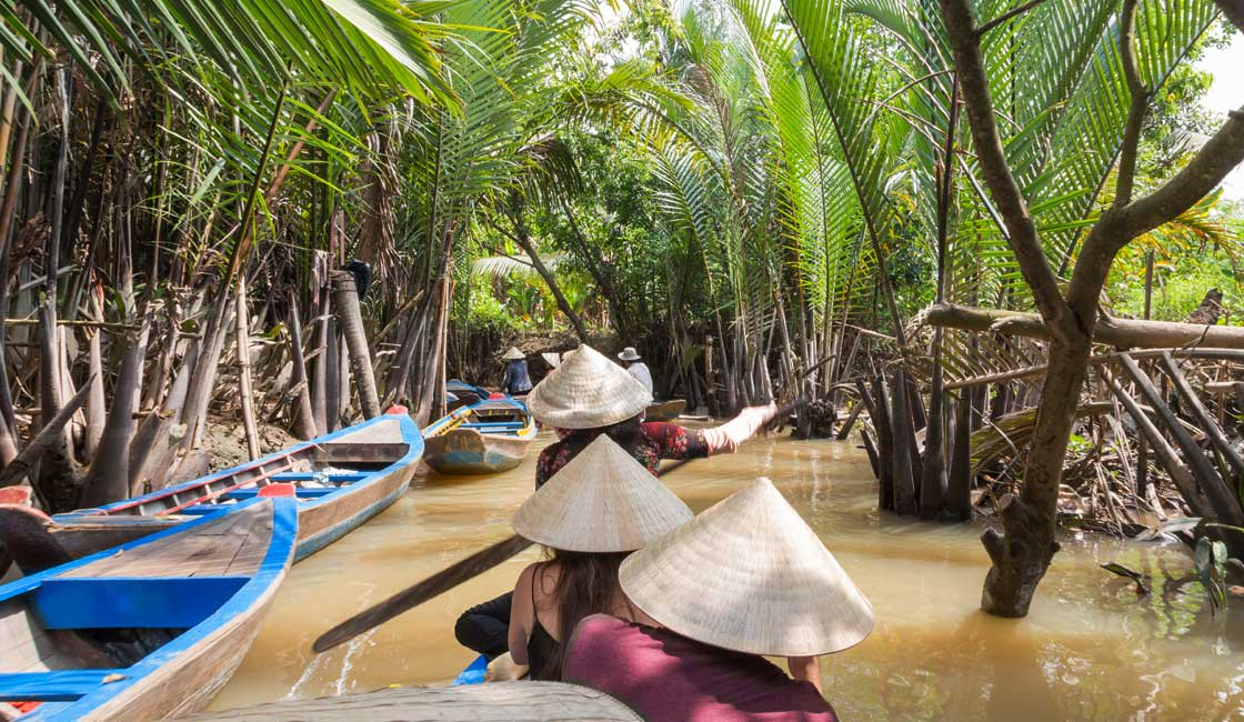 People canoing in narrow jungle cannals