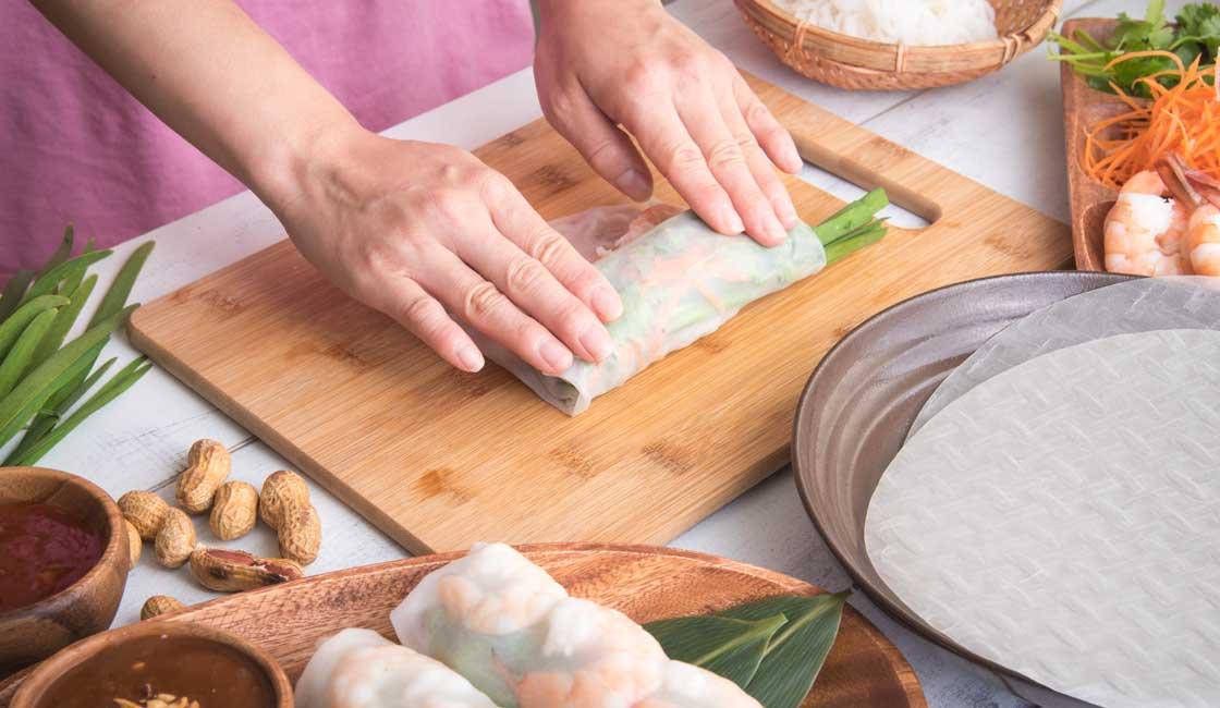 Hands assembling a spring roll