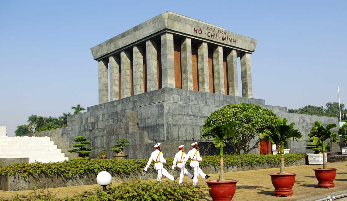 Guards marching in fron to a large mausoleum