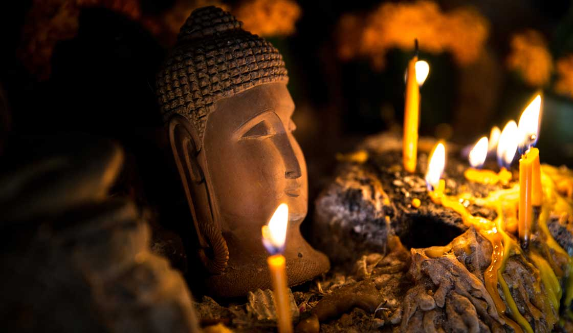 Candles lit by the Buddha head