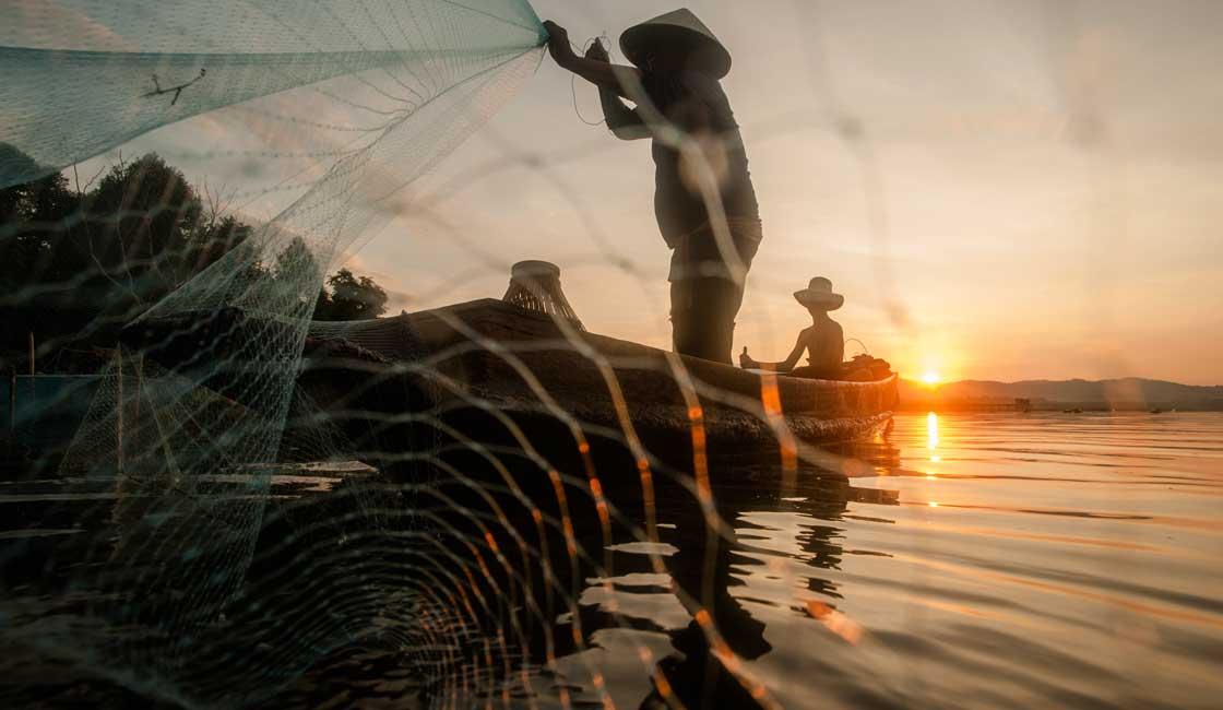 Men fishing at dawn in the Mekong