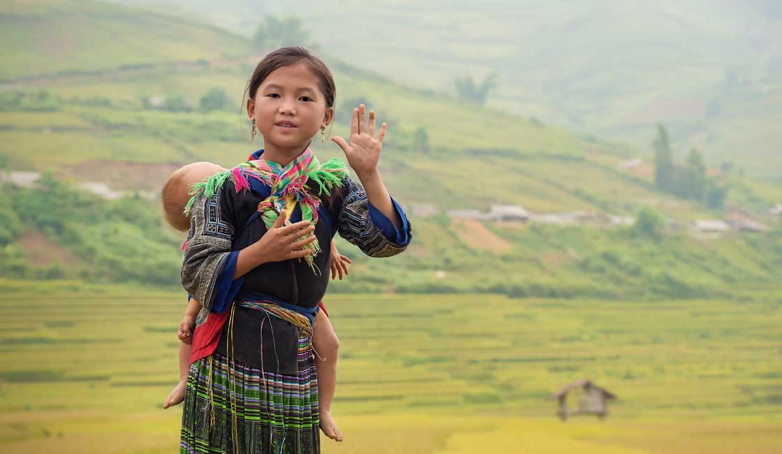 Hmong girl carrying a sleeping toddler