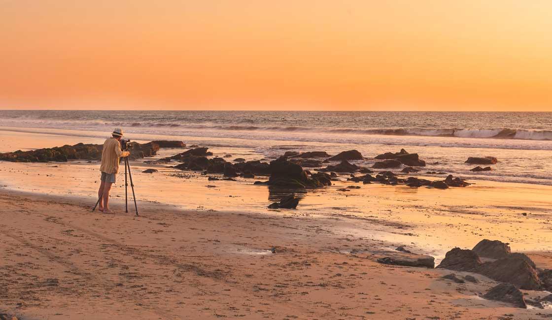 Photographer on the beach at sunset