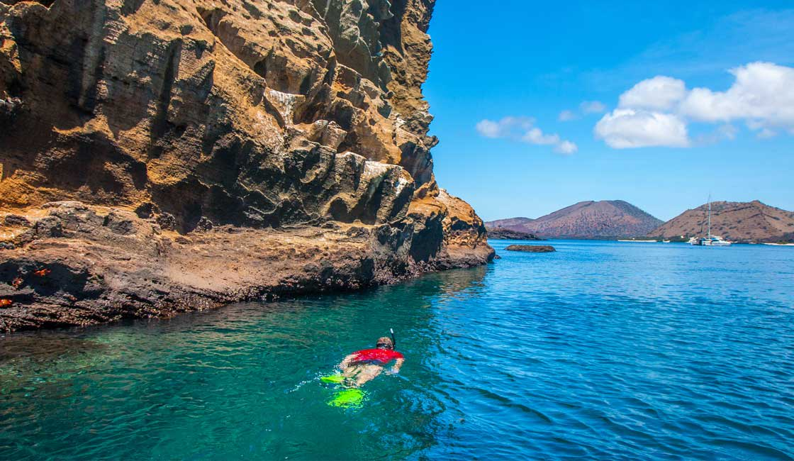 Person snorkeling by a large rock formation in Galapagos