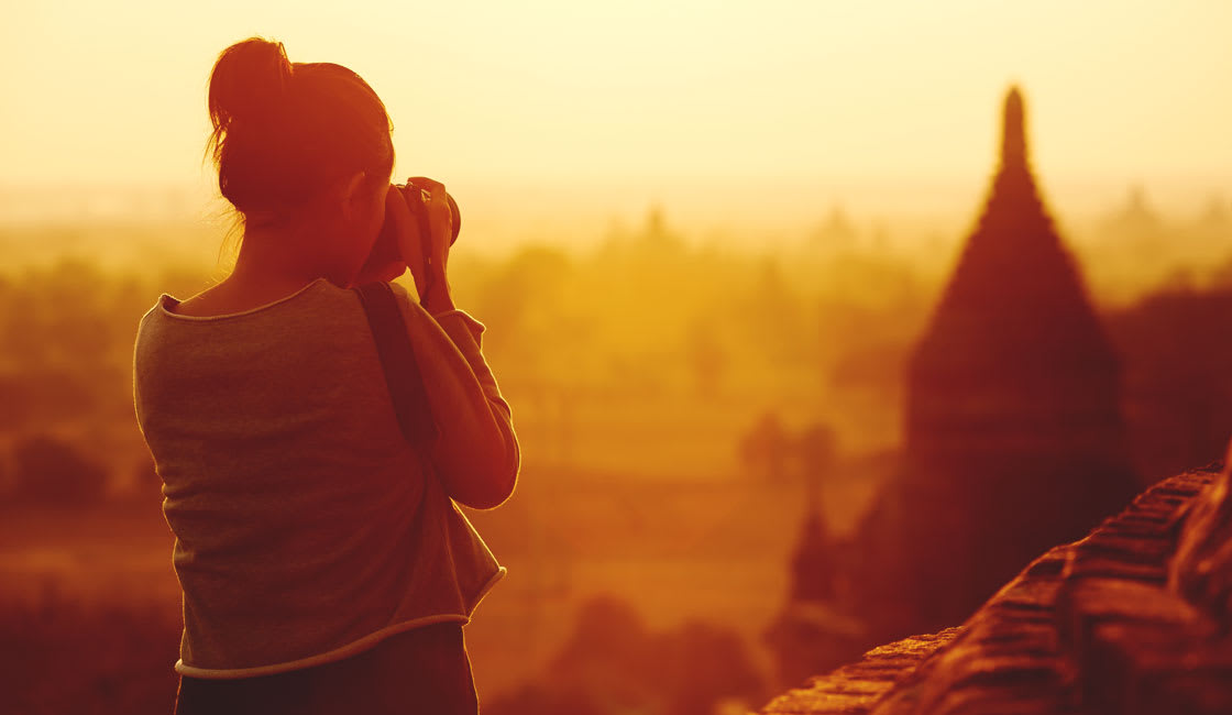 A girl photographing the temples at sunrise