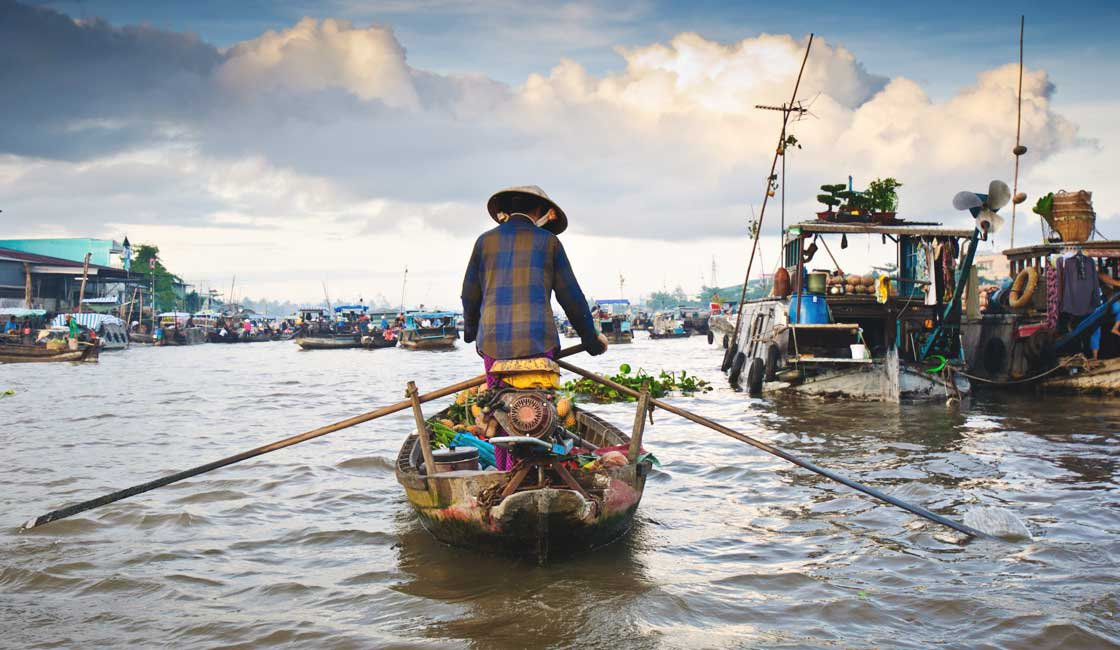 Woman rowing a sampan in the floating market