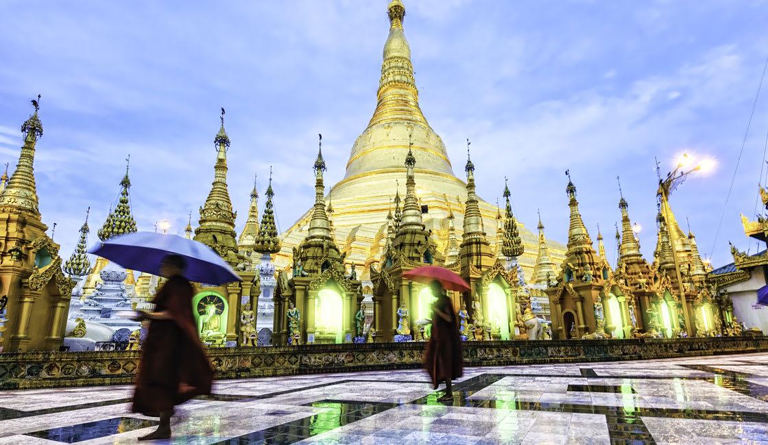 Monks walking under rain umbrella in Shwedagon Pagoda