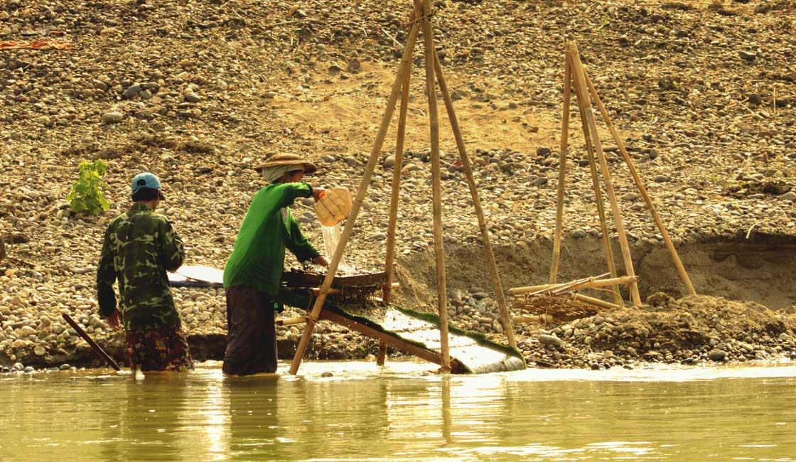 Two fishemen building a fish trap