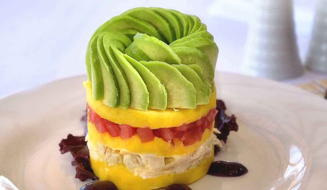 Multilayered savoury cake with avocado on top